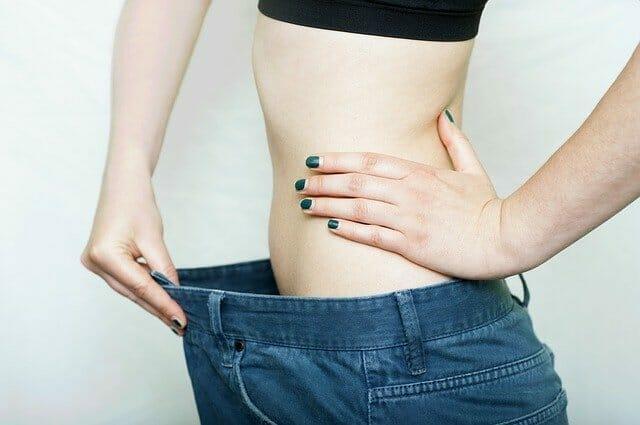 Kobieta w za dużych o kilka rozmiarów spodniach, utrata wagi