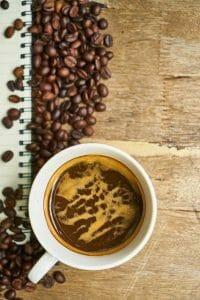 granos de café y café en una taza