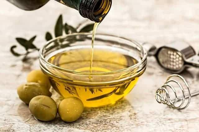 aceite vertido en un bol, aceitunas verdes a su lado