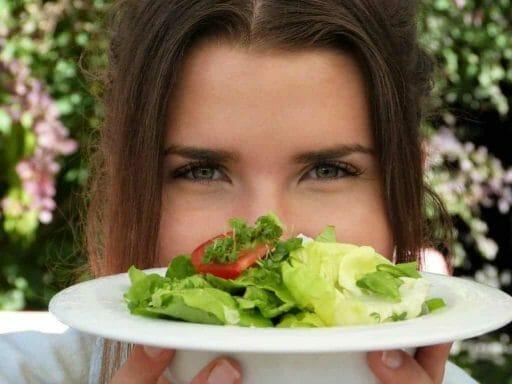 la mujer está sosteniendo un plato de ensalada