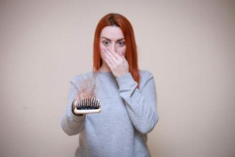 una mujer mira un cepillo lleno de pelo