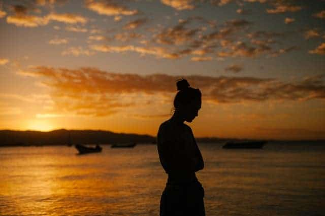 mujer triste caminando por la playa