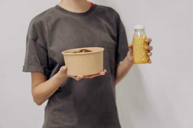 una mujer sostiene un bol de comida y un batido