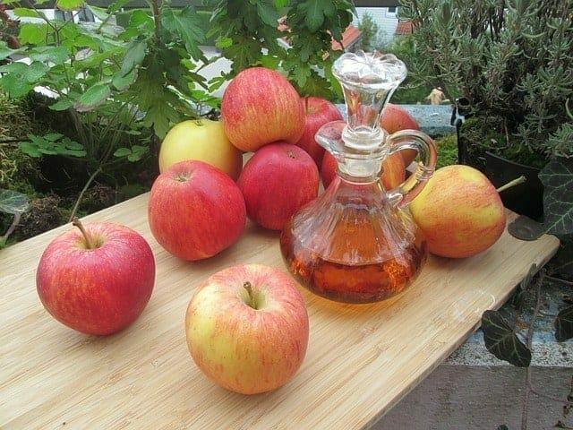 Manzanas frescas y una botella de vinagre de sidra de manzana en la mesa