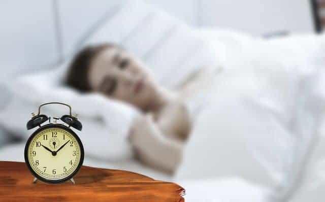 una mujer duerme con un despertador al lado de su cama