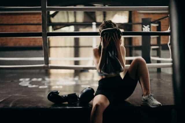 una mujer se limpia el sudor de la cara después de un entrenamiento extenuante
