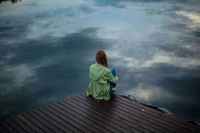 una mujer se sienta en el borde de un muelle y mira al agua