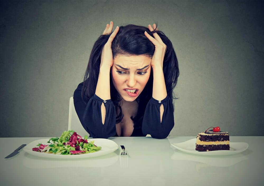 una mujer se sienta en una mesa con un plato de tarta y otro de ensalada