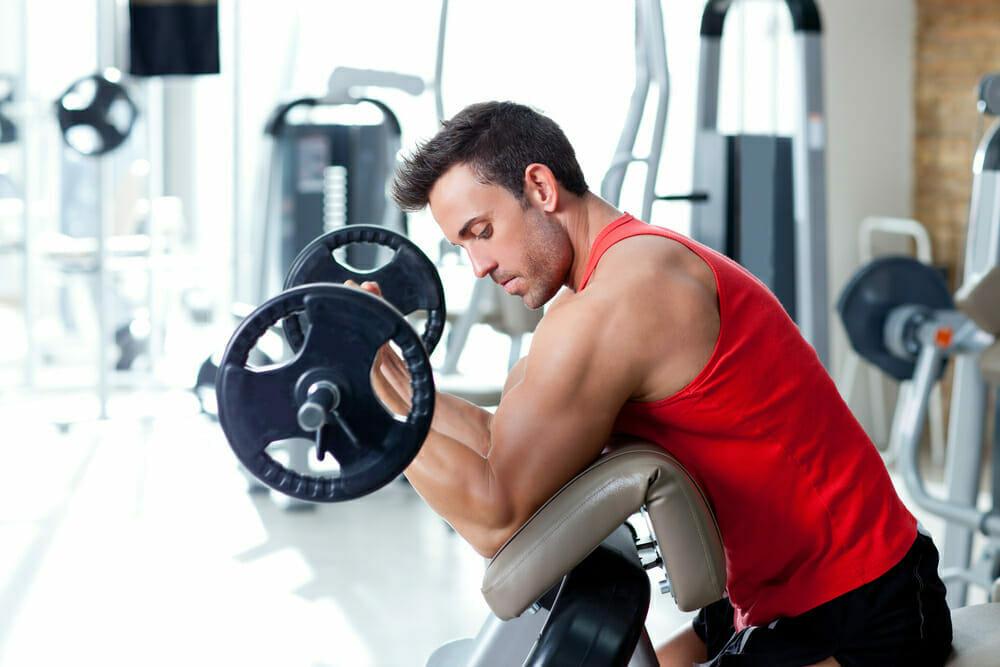 Un hombre se ejercita con una barra en el gimnasio.