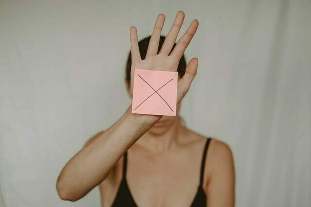 una mujer triste sostiene una caja de cartón con una x delante